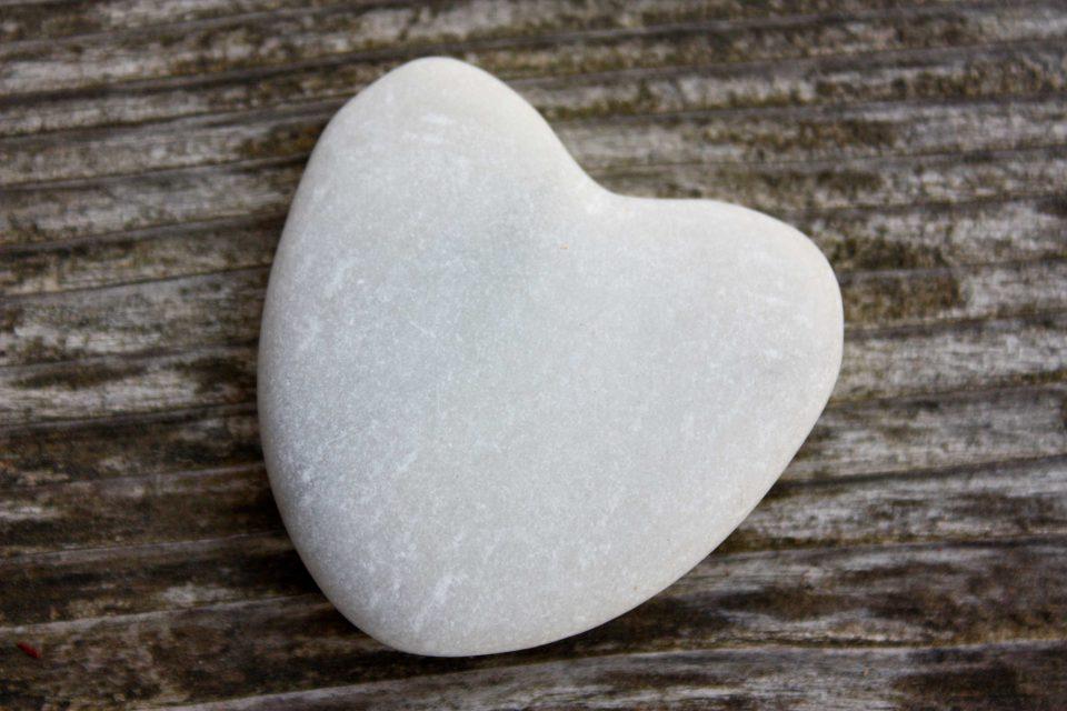 Coeur en pierre sur fond de bois