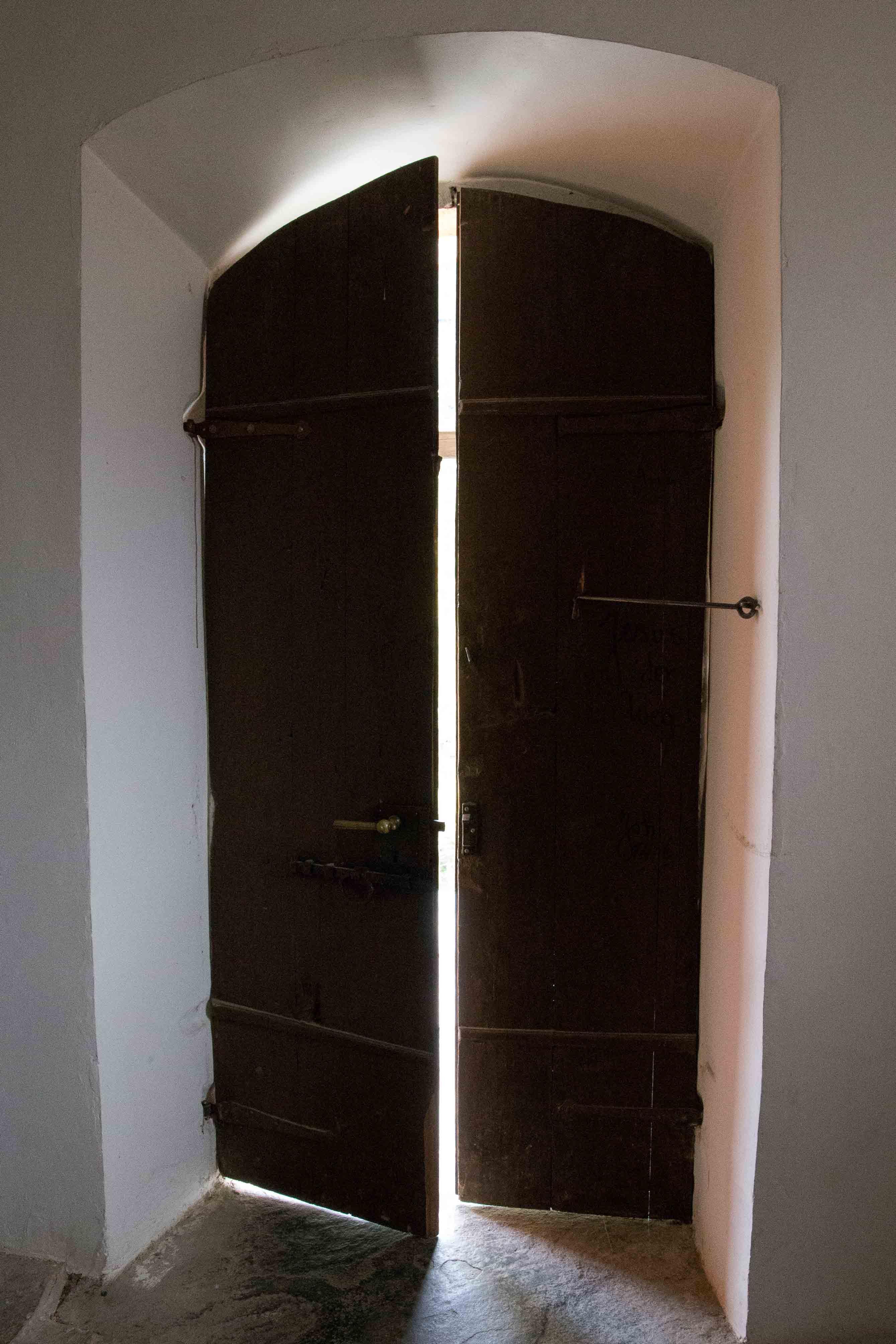 Porte en bois entrouverte sur l'extérieur et laisse entrer la lumière