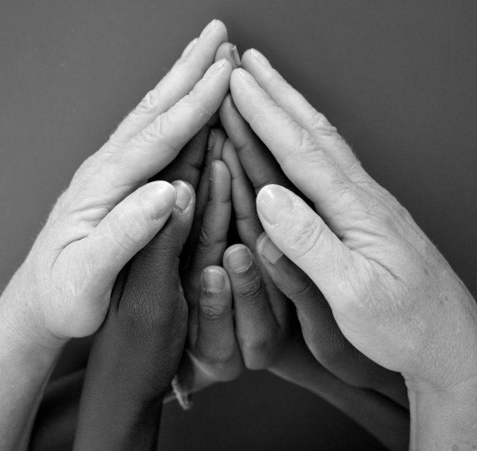Mains d'adulte entourant les mains d'enfants